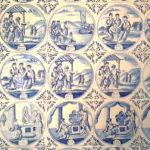 De tegelwand in het achterhuis met daarin afgebeeld het oude en het nieuwe testament.