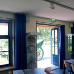 Het museumcafé met de dubbele deuren geopend naar het terras.